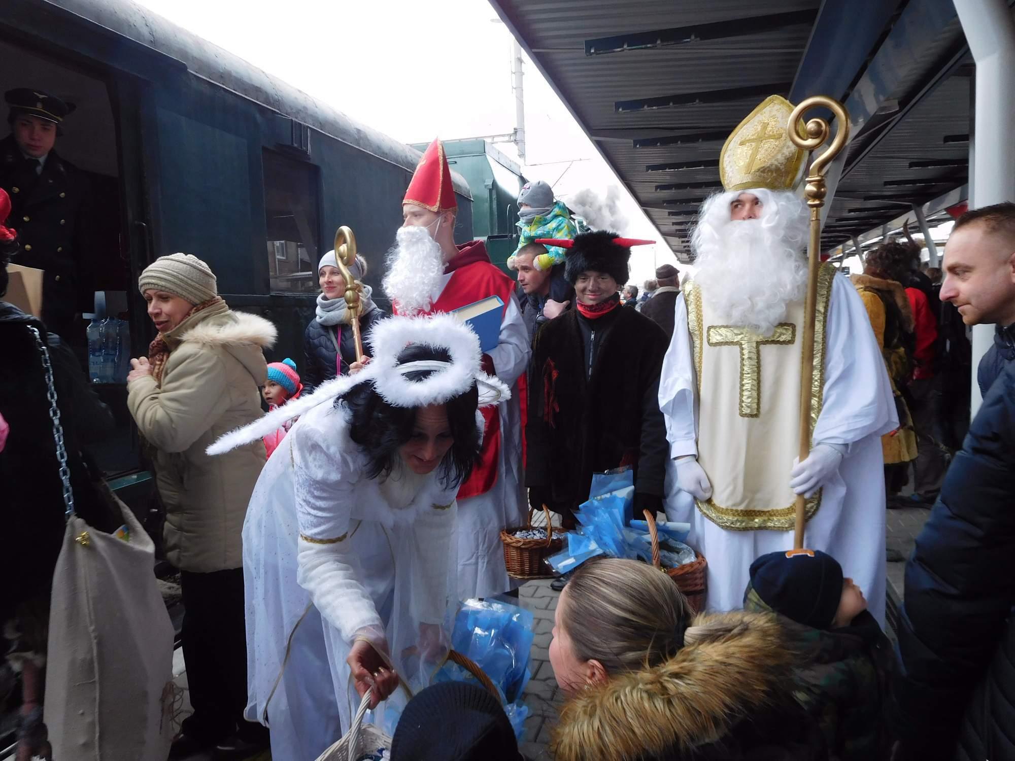 Mikulášova skupina  rozdává bonbony před parním vlakem