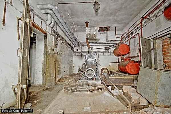 Strojovna s agregátem pro výrobu elektřiny měla tak zásadní význam, že byla opatřena protitlakovými krytovými dveřmi s pákami a také hermetickým uzavřením. Vpravo se válí zásobník se starým olejem, za ním později zazděný druhý východ.